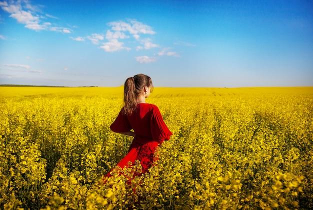 Fille dans une belle robe rouge est debout dans une boîte jaune