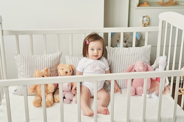 Fille dans un berceau avec des jouets dans la chambre des enfants
