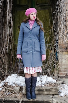 Fille dans un béret rose et un manteau gris-bleu au seuil de la vieille maison