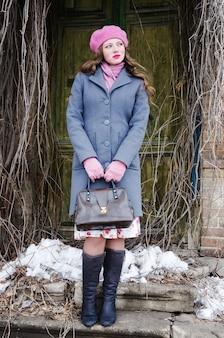 Fille dans un béret rose et un manteau gris bleu de la porte d'entrée de la vieille maison