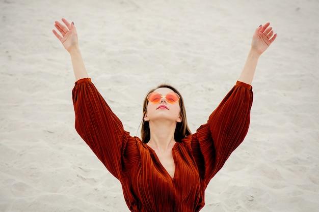 Fille dans une blouse de lunettes de soleil et bordeaux sur un sable blanc