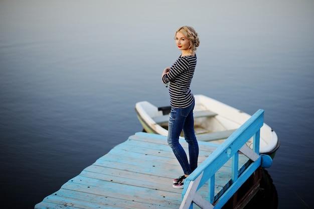 Fille dans une blouse rayée, debout sur un pont de bois sur un fond de la rivière