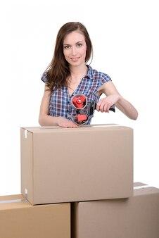 La fille dans les boîtes se tient sur un blanc.
