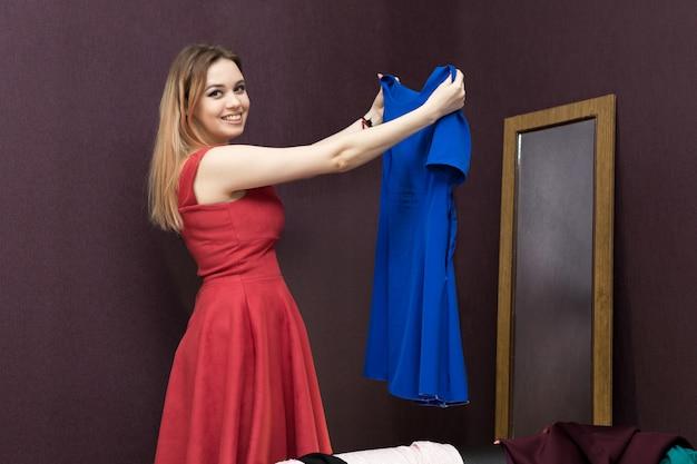 La fille dans la cabine d'essayage choisit une robe.
