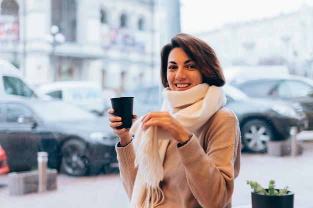 Une Fille Dans Un Café Confortable Se Réchauffe Avec Une Tasse De Café Chaud Photo gratuit