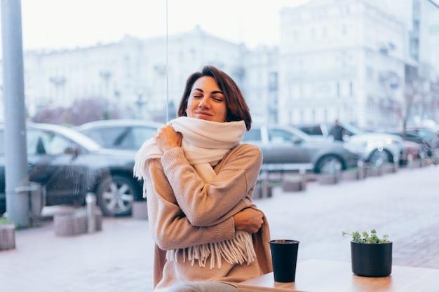 Une fille dans un café confortable se réchauffe avec une tasse de café chaud
