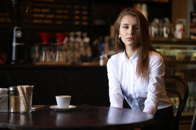 La fille dans le café prend son petit déjeuner à paris