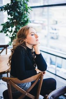 Une fille dans un café en regardant la fenêtre