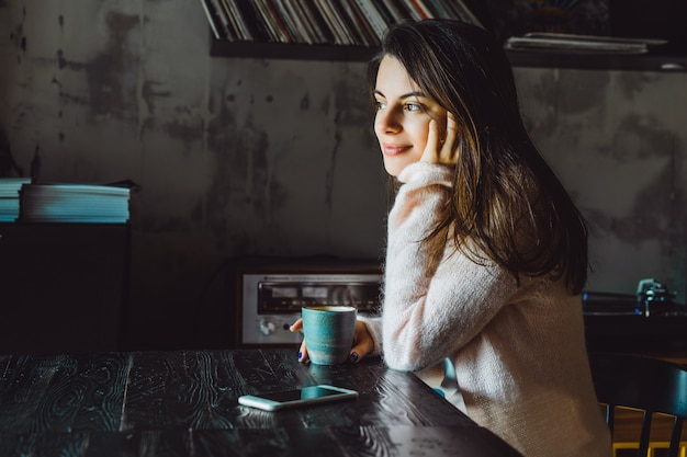 Fille dans un café avec un smartphone