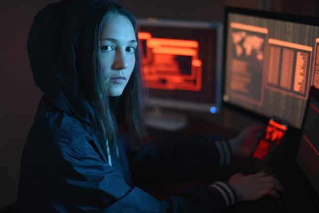 Fille dans le capot en regardant dans la caméra. attaques de hackers et fraude en ligne
