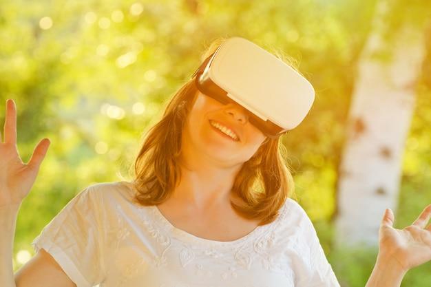 Fille dans le casque de la réalité virtuelle dans le contexte de la nature. tonifiant
