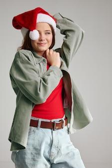 Fille dans une casquette sur un fond gris vacances noël nouvel an
