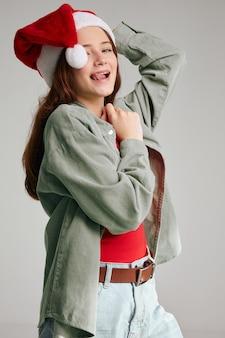 Fille dans une casquette sur un fond gris vacances veste de t-shirt jeans noël nouvel an. photo de haute qualité