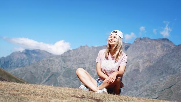 La fille dans une casquette et un short dans les montagnes est assise sur l'herbe