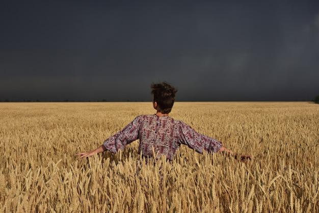 Fille dans un champ de blé avant un orage