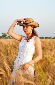 Fille dans un champ de blé en robe blanche et chapeau stetson. mise au point sélective.