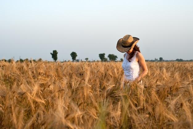 Fille dans un champ de blé en robe blanche et chapeau stetson