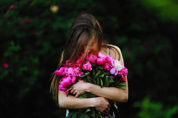 Fille dans le champ de fleurs. fille embrasse un bouquet de fleurs. bouquet de pivoine