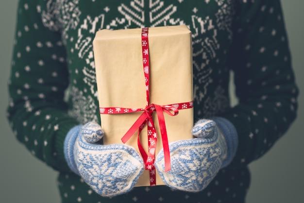 Une fille dans un chandail du nouvel an tient un cadeau. cadeaux pour hommes. joyeux noël. cadeau pour une fille. pull avec ornement de noël. robe en maille.