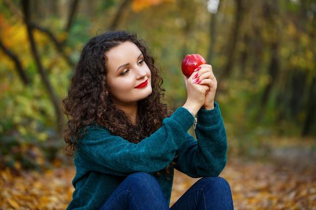 Fille dans un chandail vert et une pomme dans ses mains dans la forêt d'automne