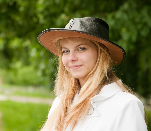 Fille dans le chapeau contre le parc