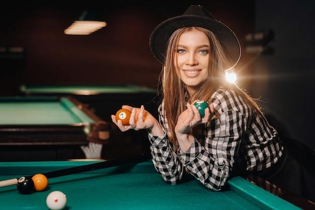 Une fille dans un chapeau dans un club de billard avec des boules dans ses mains.jouer au billard
