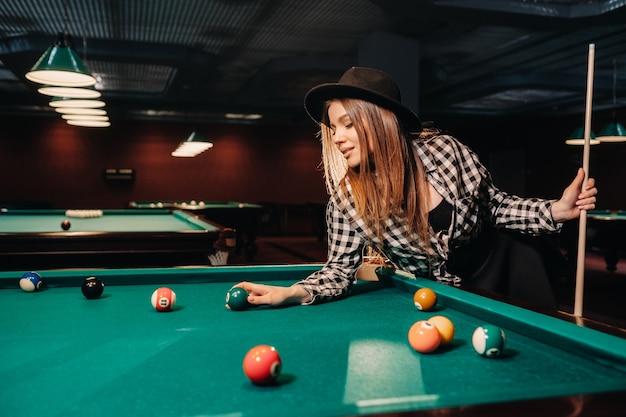 Une fille dans un chapeau dans un club de billard avec une queue et des boules dans ses mains.jouer au billard