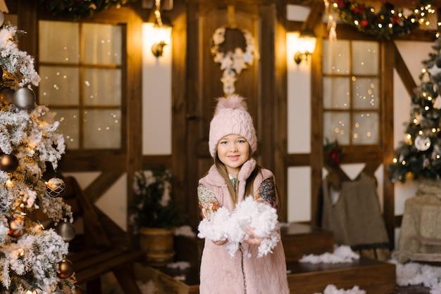Une fille dans un chapeau et un gilet rose détient de la neige artificielle