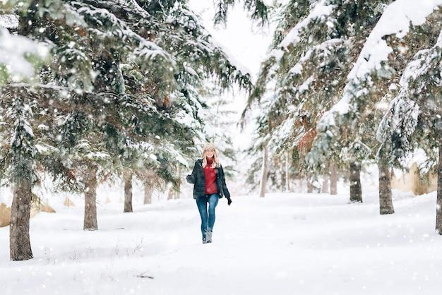 Fille dans un chapeau d'hiver à la mode avec un imprimé léopard se réjouit de la neige