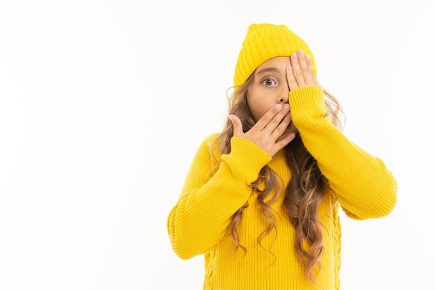 Fille dans un chapeau jaune et une veste couvrait son visage avec ses mains et regarde d'un œil sur fond blanc