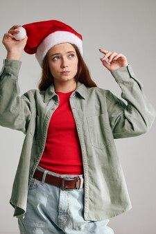 Fille dans un chapeau de noël et dans un modèle de jeans veste t-shirt rouge