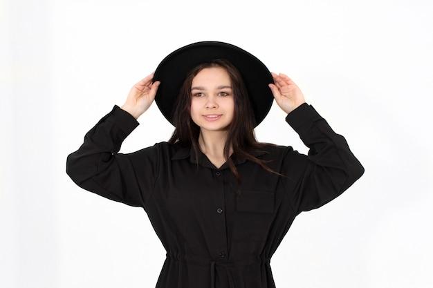 Une fille dans un chapeau noir pose et sourit sur fond blanc tenant son chapeau