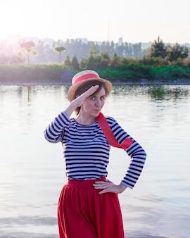 Fille dans un chapeau de paille au bord de l'eau
