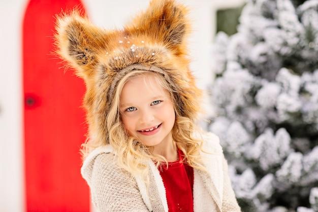 Fille dans un chapeau de renard debout devant un arbre de noël enneigé et maison rouge.