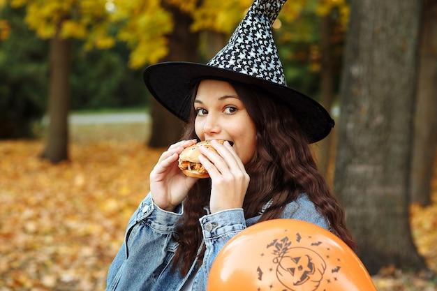 Une fille dans un chapeau de sorcière à côté d'un ballon orange pour halloween mange un hamburger dans un parc d'automne