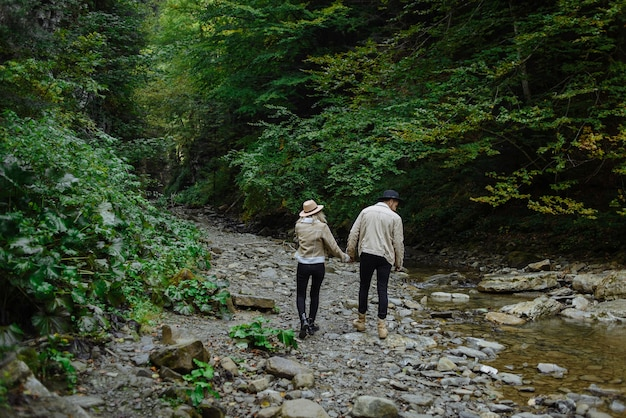 Fille dans un chapeau, une veste et un gars marchent le long d'une route forestière et se tiennent la main