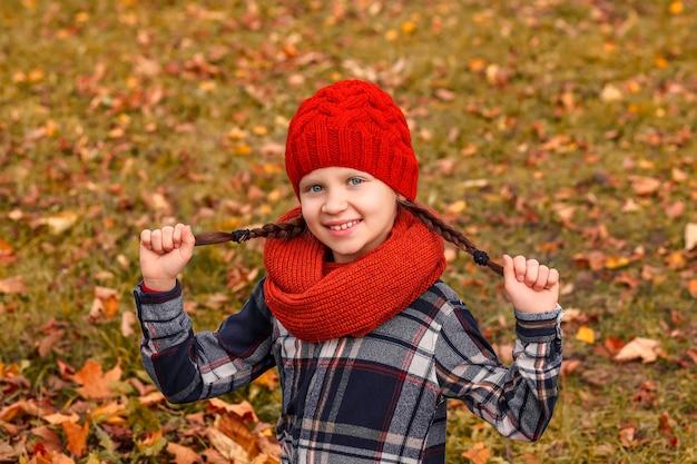 Fille dans une chemise à carreaux et un chapeau rouge sur une clairière d'automne bonnet tricoté pour la saison d'octobre