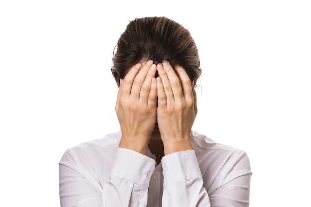 La fille dans une chemise a couvert son visage avec des mains d'isolement sur un fond blanc