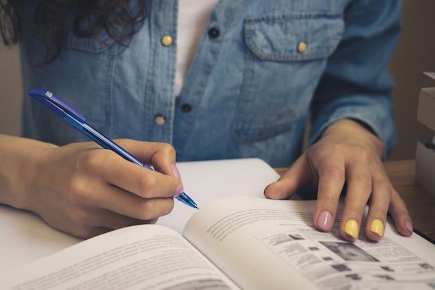 Fille dans une chemise en jean, lisant un manuel et prenant des notes