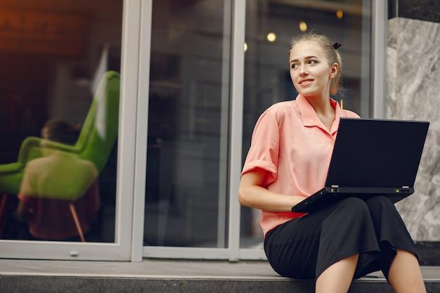 Fille dans une chemise rose assis près de la maison et utilise l'ordinateur portable