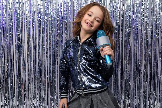 Fille dans un concours de talents avec un microphone sur un mur brillant