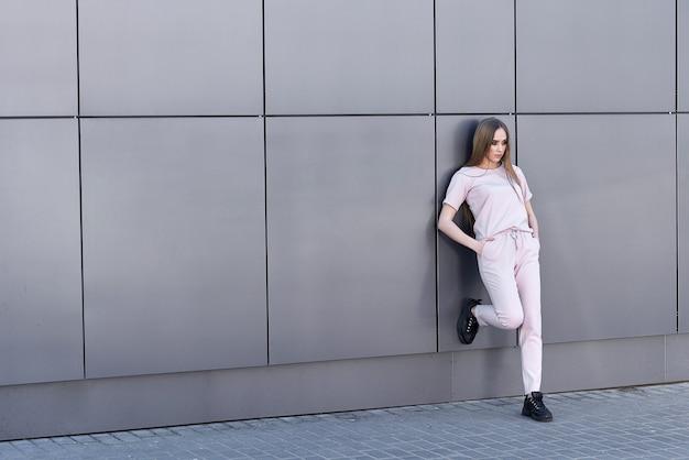 Fille dans un costume rose posant contre un mur gris