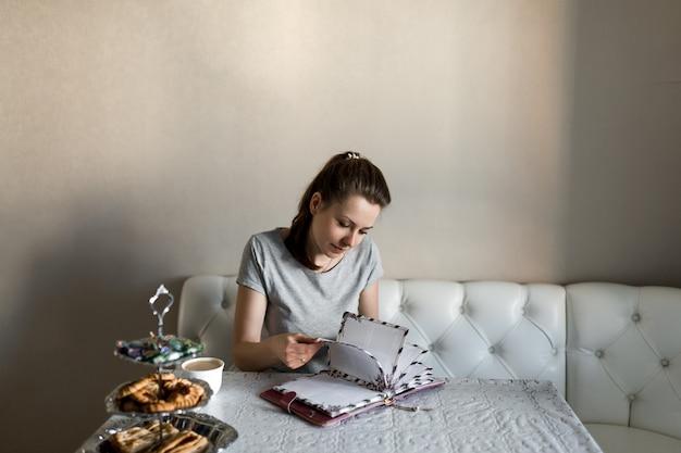 Une fille dans la cuisine est assise à table et feuillete un livre.