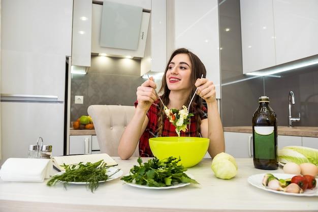 Fille dans la cuisine de manger une salade de légumes pour un mode de vie sain