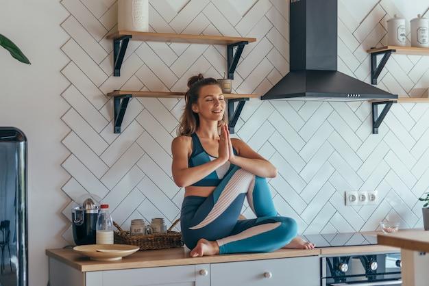 Fille dans la cuisine méditant pratiquant le yoga.