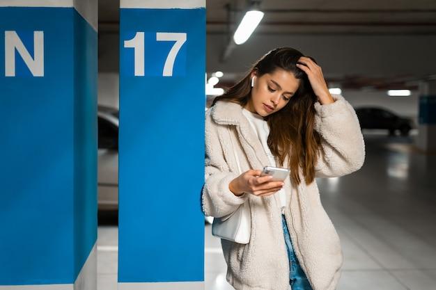 Fille dans les écouteurs sans fil et téléphone portable en mains