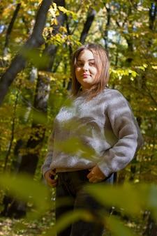 La fille dans la forêt d'automne sourit et pose. photo à travers des feuilles floues.