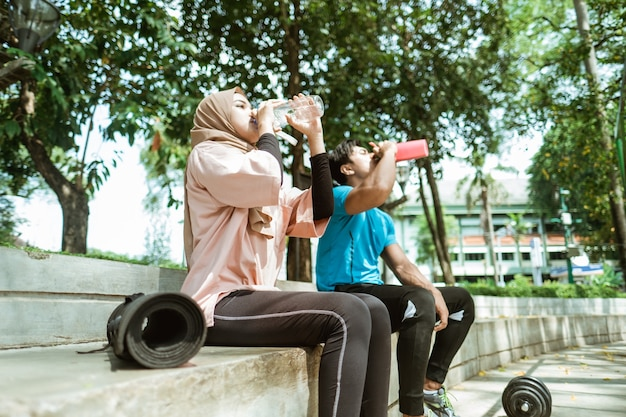 Une fille dans un foulard et un jeune homme assis à boire avec une bouteille après avoir fait des sports de plein air dans le parc