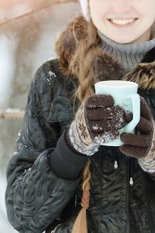 Fille dans les gants marron tenant une tasse de thé bleue, partie du visage, gros plan