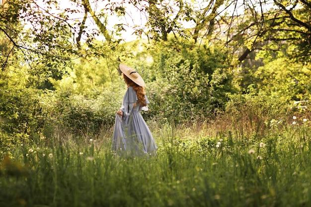 Fille dans le jardin en chapeau de paille soutient l'été